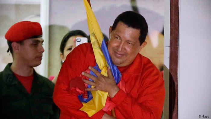 Venezuela's President Hugo Chavez holds a Venezuelan flag as he greets supporters at the Miraflores presidential palace balcony in Caracas, Venezuela, Sunday, Oct. 7, 2012. Chavez won re-election and a new endorsement of his socialist project Sunday, surviving his closest race yet after a bitter campaign against opposition candidate Henrique Capriles.(AP Photo/Fernando Llano)