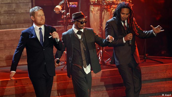 Three men in suits perform on stage (dapd)