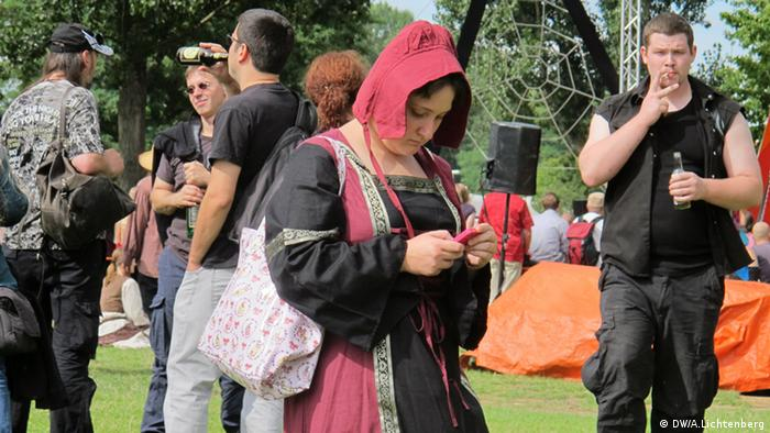 A woman in medieval costume answers her mobile phone. (DW/Arne Lichtenberg)
