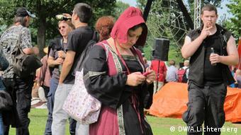 Eine verkleidete Besucherin starrt beim Mittelalterlich Phantasie Spectaculum auf ihr Handy (Foto: DW/ Arne Lichtenberg)