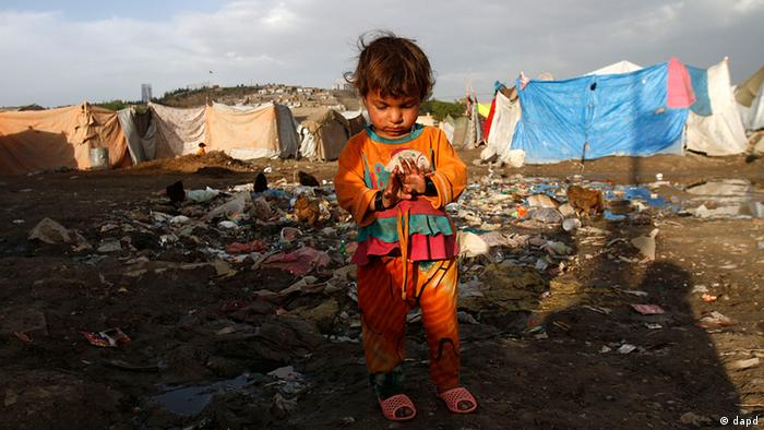 An Afghan refugee girl stands among garbage near her home in Kabul, Afghanistan, Thursday, May 17, 2012.
