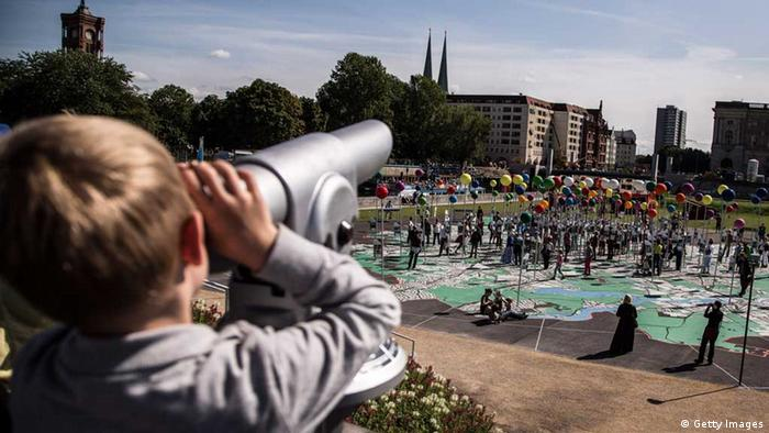 A boy looks through a telescope towards a giant map of Berlin
