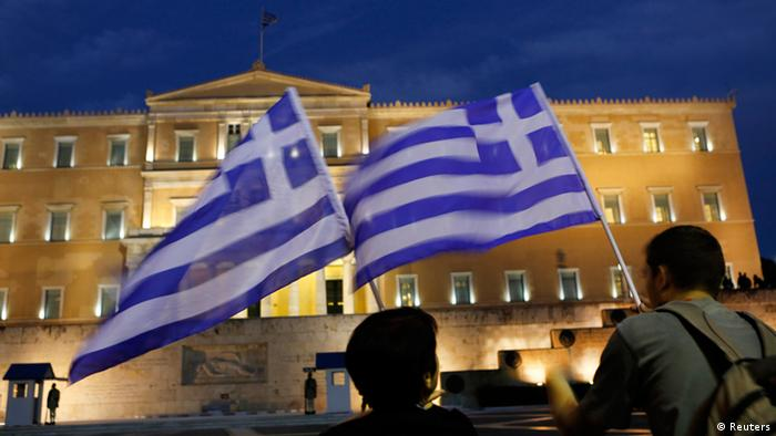 Protesters hold Greek flags in front of the Greek parliament during a demonstration against the upcoming visit by German Chancellor Angela Merkel in Athens October 8, 2012. REUTERS/Yannis Behrakis (GREECE - Tags: CIVIL UNREST POLITICS)