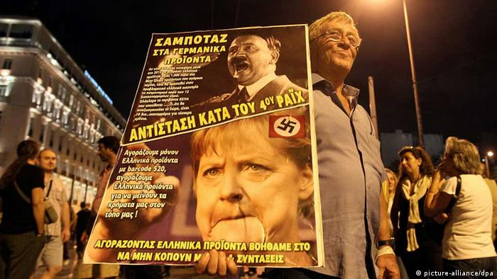 A demonstrator holds a poster depicting Adolf Hitler and German Chancellor Angela Merkel during a protest in front of the Parliament building against new austerity measures in Athens (c) dpa - Bildfunk
