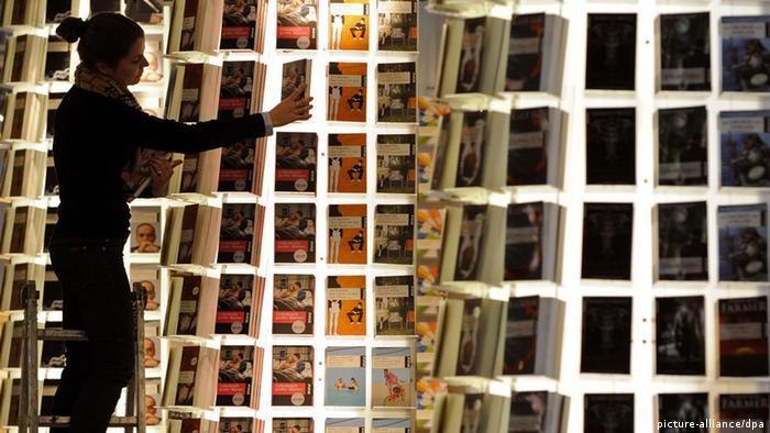 Eine Frau, die auf einer Leiter steht, räumt am Dienstag (14.10.2008) auf dem Gelände der Frankfurter Buchmesse an einem Stand Bücher in ein Regal ein (Illustration), im Vordergrund rechts ein weiteres Regal. Die Messe wird am Mittwoch (15.10.2008) offiziell eröffnet und soll bis zum kommenden Wochenende mehrere hunderttausend Besucher anziehen. Foto: Marijan Murat dpa/lhe +++(c) dpa - Bildfunk+++