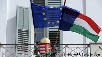 EU and Hungarian flags fly in front of a Hungarian crest Photo: ATTILA KISBENEDEK/AFP/Getty Images