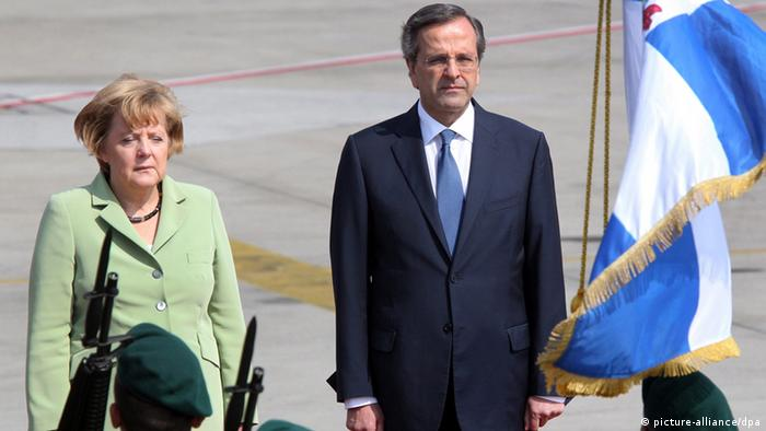 epa03426406 Greek Prime Minister Antonis Samaras (R) welcomes German Chancellor Angela Merkel (L) at Athens International Airport, Greece, 09 October 2012. German Chancellor Angela Merkel travelled to Greece for talks with leaders eager for her support to avoid bankruptcy and remain in the eurozone as angry Greeks prepare to protest against her austerity drive. EPA/PANTELIS SAITAS pixel