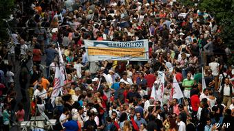Protesters hold a banner which reads in Greek Revolt during a demonstration in Athens on Tuesday, Oct. 9, 2012. In heavy security measures and a mass protest, German Chancellor Angela Merkel arrived Tuesday for her first visit to Greece since the eurozone crisis began there three years ago. Her five-hour stop is seen by the Greek government as a historic boost for the country's future in Europe, but by protesters as a harbinger of more austerity and hardship.(Foto:Petros Giannakouris/AP/dapd)