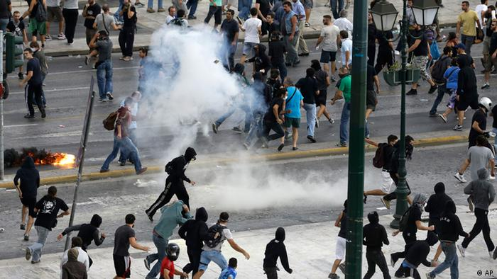 Protesters run away from tear gas during clashes in front of the parliament in Athens on Tuesday Oct. 9, 2012. Photo:Dimitri Messinis/AP/dapd