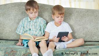 Zwei Jungen sitzen lesend auf einem Sofa einer mit Printbuch (l.), der andere mit E-Reader (© AndreyPS - Fotolia.com)