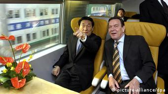 Der chinesische Ministerpräsident Zhu Rongji (l) zeigt am 31.12.2002 bei der Jungfernfahrt des Transrapids in Schanghai mit Bundeskanzler Gerhard Schröder auf die Geschwindigkeitsanzeige im Wageninneren. Der Transrapid hat seinen ersten Test bestanden: Für die 31 Kilometer von Schanghai zum Flughafen Pudong brauchte die Bahn weniger als acht Minuten. Der Zug erreichte dabei stellenweise eine Spitzengeschwindigkeit von 431 Stundenkilometern. Nach der erfolgreichen Jungfernfahrt des Transrapids plant China den Bau weiterer Strecken. Zhu Rongji gab Schröder eine Zusage über eine Verlängerung der bestehenden Trasse der Magnetschwebebahn auf 300 Kilometer.
