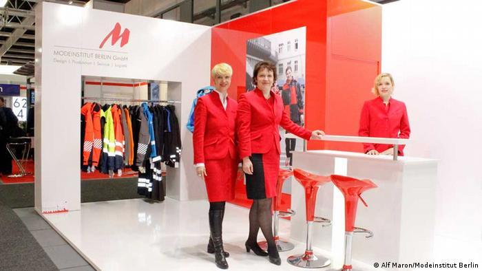 Two businesswomen stand next to each other at a trade fair