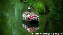 Tourists on a boat make their way through the Spreewald region near Burg, eastern Germany, on May 21, 2012. Meteorologists forecast temperatures up to 30 degrees for the following days in the region, which is protected as a biosphere reserve. AFP PHOTO / PATRICK PLEUL GERMANY OUT (Photo credit should read PATRICK PLEUL/AFP/GettyImages)