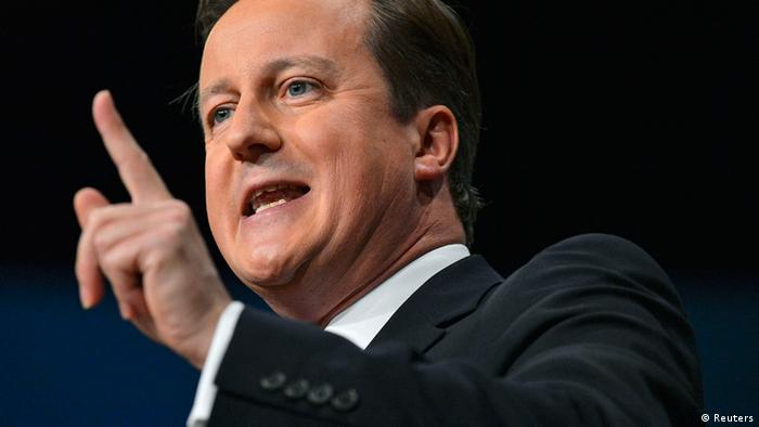 Prime Minister David Cameron of the UK raises his figner while wearing a black suit. (Photo: REUTERS/Toby Melville)