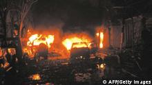 Buildings and cars are on fire after a bomb blast in tourist site of Kuta, Bali 13 October 2002. At least 53 people including 10 foreigners, were killed when a bomb exploded in a popular nightclub on the Indonesian resort island of Bali. AFP PHOTO/ DARMA (Photo credit should read DARMA/AFP/Getty Images)