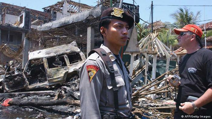 A foreign tourist (R) looks at the destroyed building of what remains of the Padi club the day after a bomb blast in Denpasar, on the Indonesian island of Bali, 13 October 2002. The huge car bomb ripped through two bars late 12 October packed with foreign tourists on the Indonesian resort island of Bali, killing at least 182 people in an attack blamed on terrorists  (Photo: AFP Getty Images)