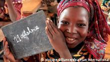 HANDOUT - Ein Mädchen in Niger, das sich freut, eine Schule besuchen zu dürfen, hält eine kleine Tafel, auf der «11. Oktober» geschrieben steht, in ihrem Klassenzimmer hoch (undatiertes Foto). Die internationale Hilfsorganisation «Plan» hat die Vereinten Nationen davon überzeugt, dass die Welt auch einen Weltmädchentag braucht. Denn Mädchen werden in vielen Ländern benachteiligt und haben nicht die gleichen Chancen wie Jungen. Der Tag ist für alle Mädchen weltweit, also auch für die Mädchen in Deutschland. Foto: Plan International - ACHTUNG: Nur zur redaktionellen Verwendung und nur mit Nennung der Quelle: «Plan International»