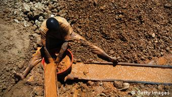 A man washes rocks in an open pit gold mine LIONEL HEALING/AFP/Getty Images