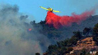 A plane drops water to help extinguish a forest fire