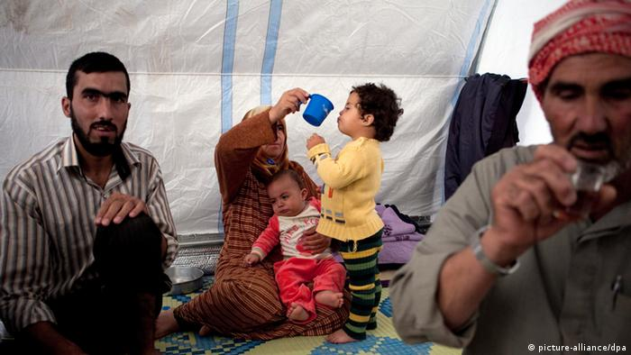 Syrian refugee woman tending to her small children at a camp