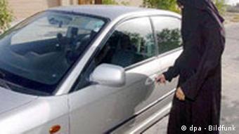 veiled woman unlocking a car