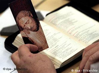 A modern Bible and bookmark picturing Jesus on the cross