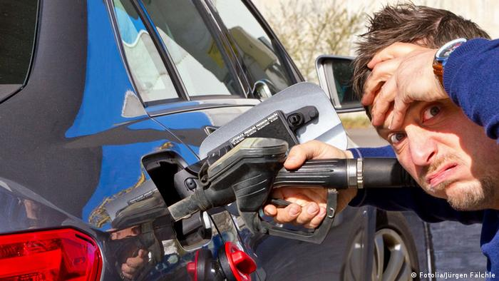 Frustrated man filling up the tank of his car