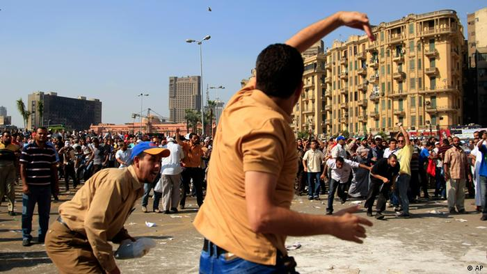 A protester throws a stone after scuffles broke out between groups of several hundred protesters in Tahrir Square