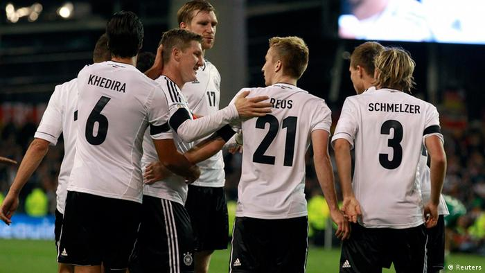 german players celebrate Germany's Marco Reus (21) is congratulated by his team mates after scoring against Ireland during the 2014 World Cup qualifying soccer match at the Aviva Stadium in Dublin October 12, 2012. REUTERS/Cathal McNaughton (IRELAND - Tags: SPORT SOCCER)