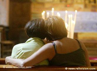 Two women embrace in front of lit candles