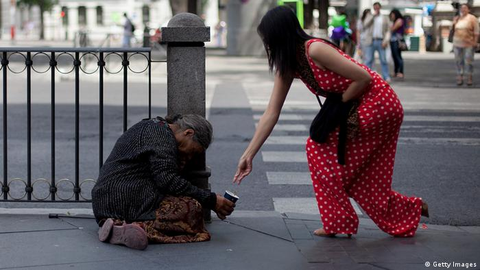 Woman gives alms to homeless in Madrid