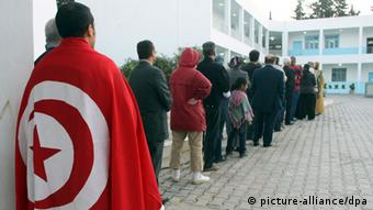 epa02977467 Tunisians wait in a line on 23 October 2011 to cast their votes. Tunisians go to the polls Sunday in the country's first ever free elections, nine months after a revolution that forced out the country_s dictator, setting an example for the entire Arab world. Around 11,000 candidates are competing in the election of a 217-member constituent assembly, which will draw up a new constitution, under which presidential and parliamentary elections will be held. EPA/STRINGER