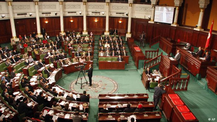 Members of constituent assembly listen to Tunisian Prime Minister Hamadi Jebali, standing at right, as he presents his government in Tunis, Thursday, Dec. 22, 2011, while Assembly President, Mustapha Ben Jaafar, 2nd right, looks on in Tunis, Thursday, Dec. 22, 2011. Jebali presented his coalition government, giving some key ministries to a moderate Islamist party, which dominated the country's first post-uprising elections. The new coalition Cabinet presented Thursday, is the first since the country's first post-uprising elections. (Foto:Hassene Dridi/AP/dapd)