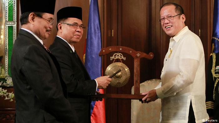 Philippine President Benigno Aquino (R) receives a gong from Moro Islamic Liberation Front (MILF) Chairman Al Haj Murad (C) and MILF Peace Panel Chief Mohagher Iqbal before the historic signing of the framework agreement between the Philippine government and the MILF in the Malacanan Palace in Manila, October 15, 2012. REUTERS/Xinhua/Rouelle Umali/Pool (PHILIPPINES - Tags: POLITICS)