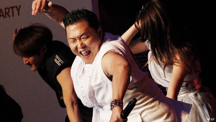 South Korean rapper Psy, centre, sings the popular Gangnam Style song, performing during his concert in Busan, South Korea, Saturday, Oct. 6, 2012. (AP Photo/Ahn Young-joon)