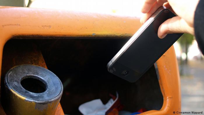 Man sieht eine Hand, die ein Handy in den Mülleimer wirft.