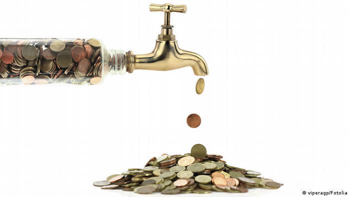Geldmünzen fallen aus einem Wasserhahn