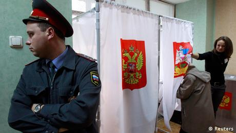 A police offer stands next to voting booths in Russia during local elections in 2012 (Photo: Sergei Karpukhin)