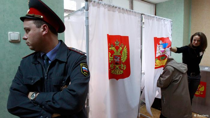 A police officer stands next to voting cabins during local elections in the Moscow. (Photo: REUTERS/Sergei Karpukhin)