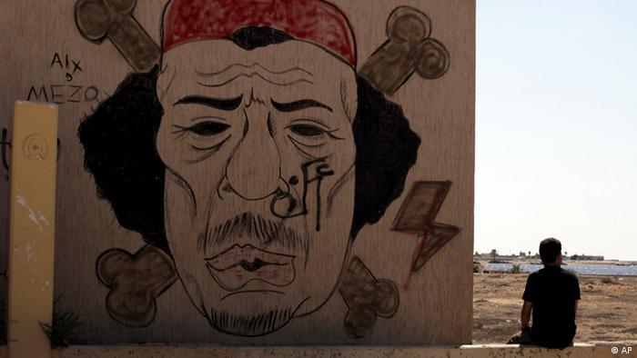 Líbio senta-se junto a graffiti de Kadhafi, em Bengazi, no dia da morte do líder líbio, a 20 de Outubro