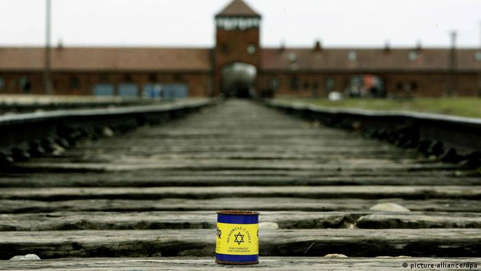 A memorial candle encased in a tin sits on the train tracks at Birkenau