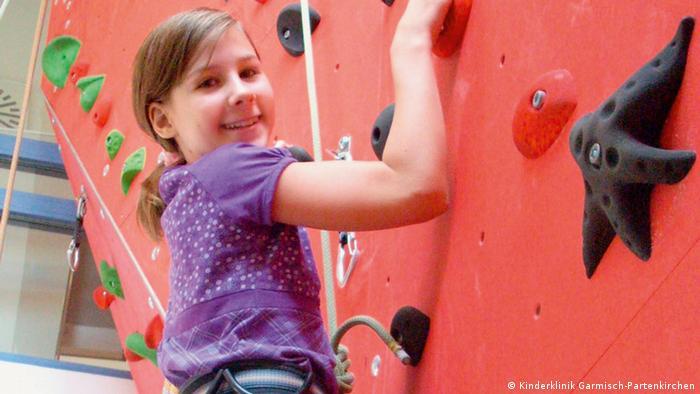 Djevojčica na zidu za penjanje