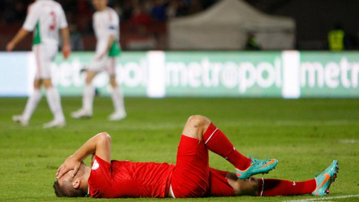 Turkey's Tunay Torun lies on the ground because of his injury during their 2014 World Cup qualifying soccer match against Hungary at Ferenc Puskas stadium in Budapest REUTERS/Bernadett Szabo (HUNGARY - Tags: SPORT SOCCER)