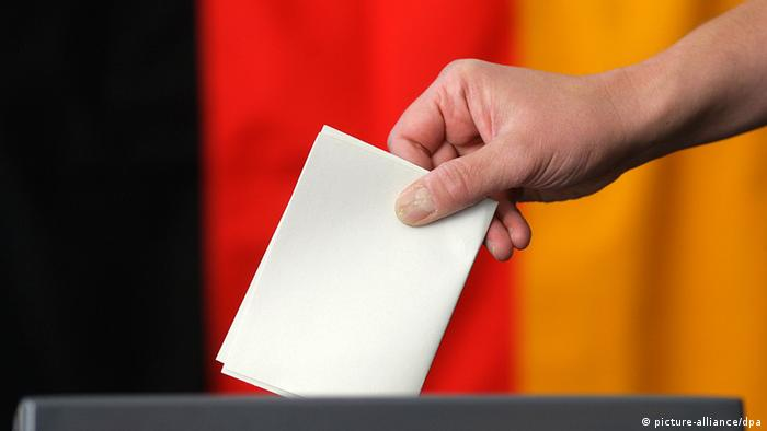 A close-up of a hand casting a paper ballot into a box, with the German flag in the background.