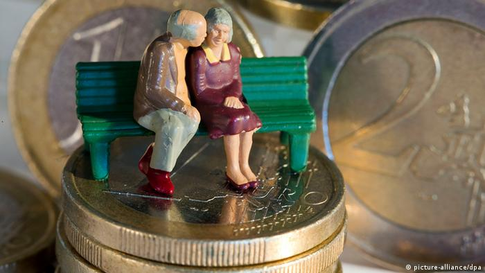 Two miniature pensioners sitting on a bank standing on a pile of euro coins Photo: Jens Büttner dpa/lmv