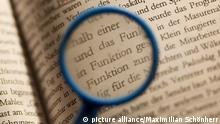 Eine kleine blaue Lupe vergrößert im Text eines politischen Buchs das mehrfach auftauchende Wort funktion. Aufgenommen in Köln am 04.04.2012. Foto: Maximilian Schönherr pixel