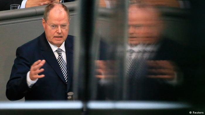 A pane of glass doubles the image of a bald, middle-aged politician in a business suit (Photo: REUTERS/Tobias Schwarz)