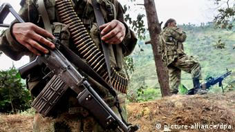 Members of the FARC guerilla patrol on a road (Photo: Christian Escobar Mora)