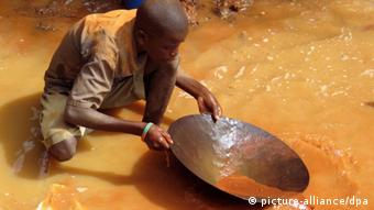 A boy pans for gold in a river