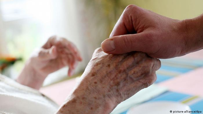A young person's hand holding an old person's hand in a hospice. (Photo: Oliver Berg, dpa)